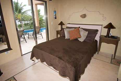 Sliding glass doors open onto the poolside patio area from the second bedroom