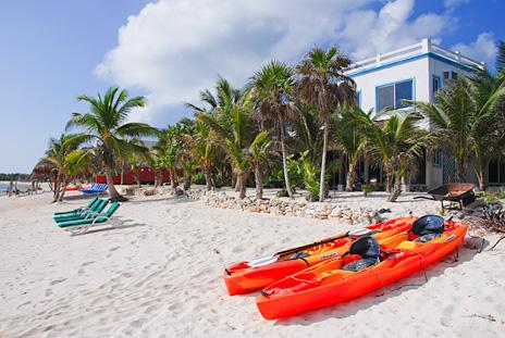 Kayaks await on the beach at Villa Tres Delfines luxury villa on Soliman Bay, Riviera Maya, Mexico