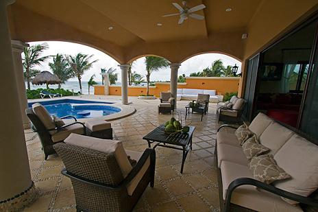Enjoy margaritas on the poolside patio at hacienda caracol beach rental villa