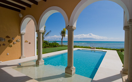 Arches frame the swimming pool and Caribbean beyond at Villa Kukulkan