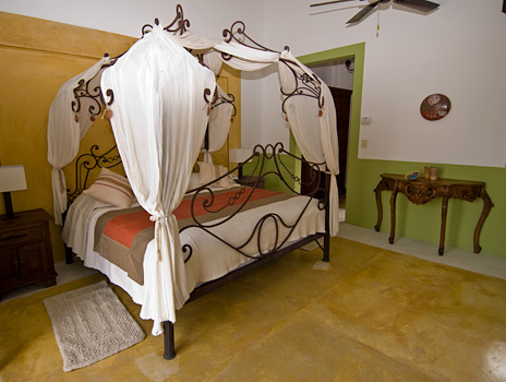 This bedroom at Hacienda Kukulkan has a king canopy bed
