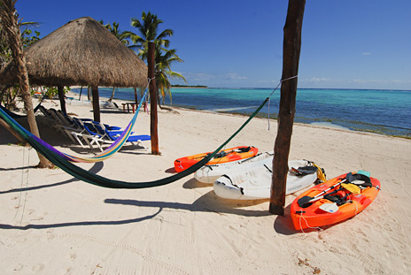 Hammocks and kayaks on the beach at Villa Margarita vacation rental home on Soliman Bay, Riviera Maya, Mexico