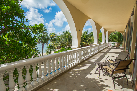 Arches on the second level patio provide a perfect frame of the sea and palms at Villa Orquidea luxury rental property