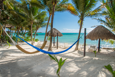 Beach chairs aond palapas on the beach at Villa Palmeras Soliman vacation rental home