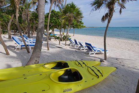 Sea kayaks await on  beach at Playa del Caribe vacation villa on South Akumal Bay