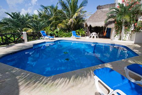 Lounge chairs and palapa at Sea Gate  4 BR Akumal vacation rental villa on the Riviera Maya