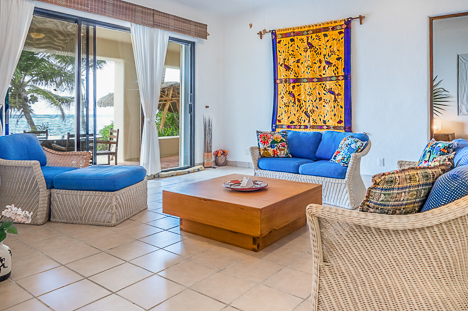 Sliding glass doors go from the living room to the beach at Akumal Sunrise 2 BR vacation rental villa