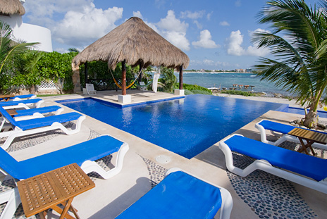 Lounge chairs surround the pool at  Villa de Vallhalla 6 bedroom luxury vacation rental home in Akumal