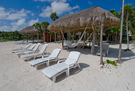 Lounge chairs line the beach at Casa Yamulkan vacation rental home on Soliman Bay