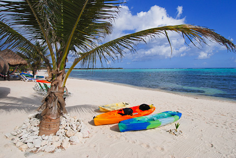 Sea kayaks  on the beach at Nah Yaxche vacation rental bungalow on Soliman Bay