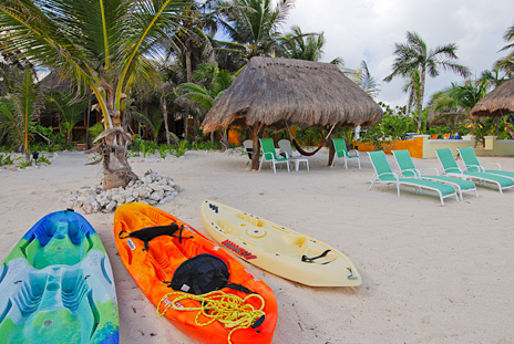 a view of the palapa, kayaks and lounge chairs at  Nah Yaxche vacation rental villa on Soliman Bay